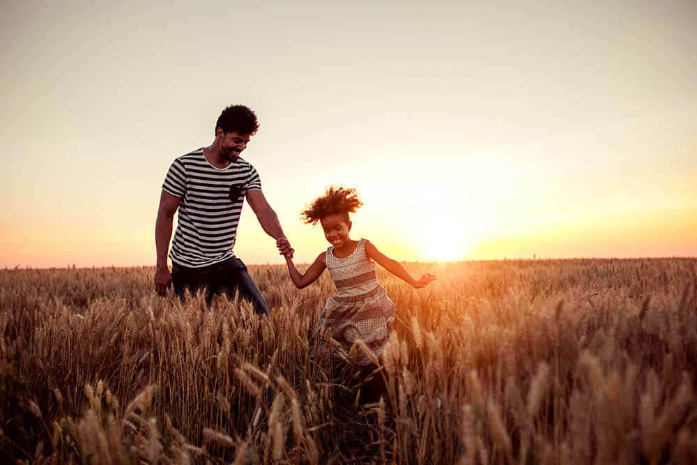 Father and young daughter in a field