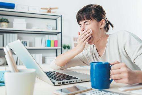tired woman yawning while looking at her computer