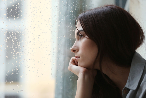 depressed young woman staring out the window on a rainy day